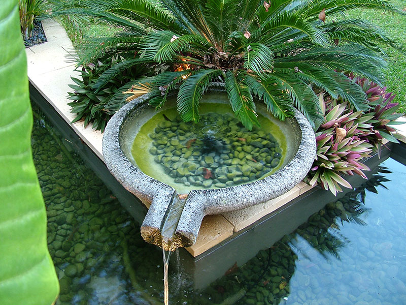 Cultivart water feature in tropical garden nedlands with lavastone bowl overflowing to pond