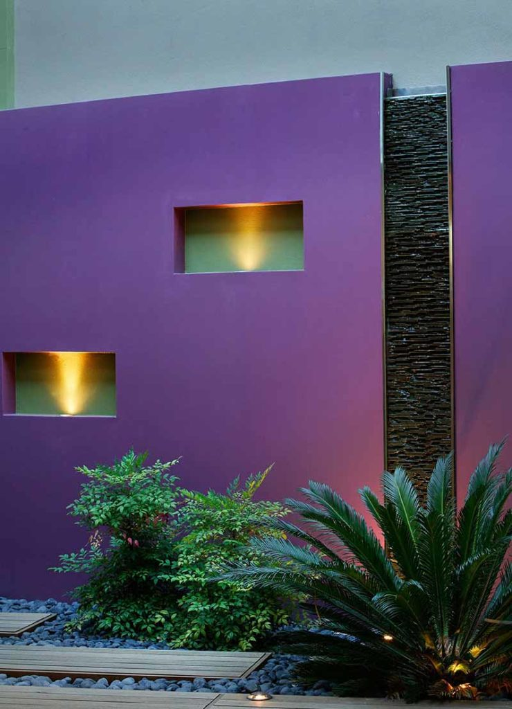 coloured light wall in subiaco courtyard with decking and pebbles