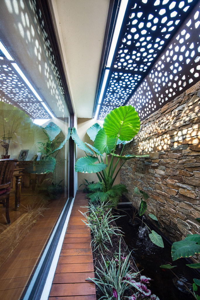 dining room atrium with laser cut roof and stone wall water feature