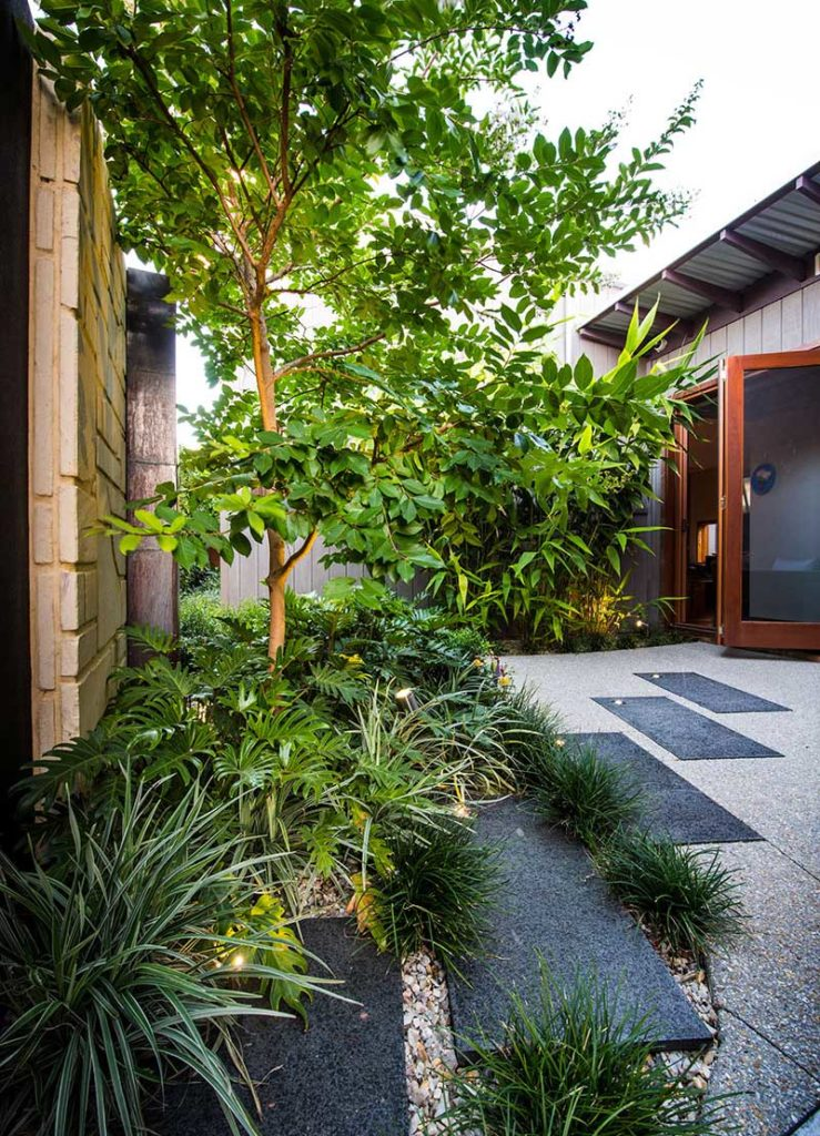 Courtyard design with limestone and copper water wall, granite steppers and washed aggregate paving in contemporary setting