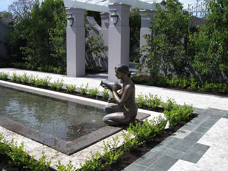 formal water feature with bronze sculpture of woman