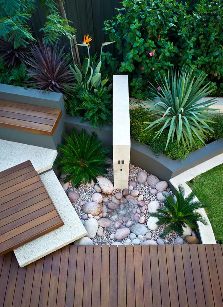 modern blade water wall beach garden in halls head with daybed, decking, and travertine cladding