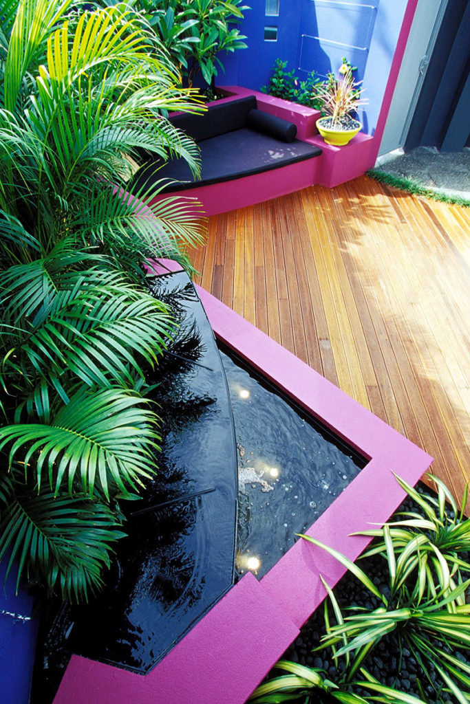 bright pink courtyard with blue walls and tropical plants