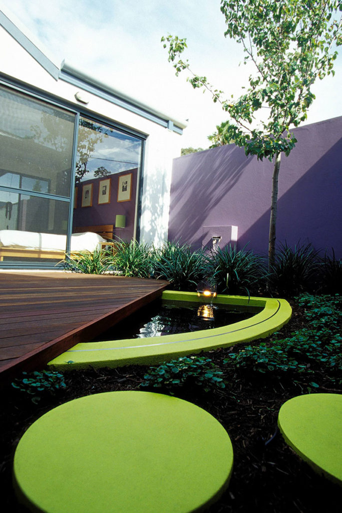 bold little courtyard with brightly coloured circular steppers and D shaped pond