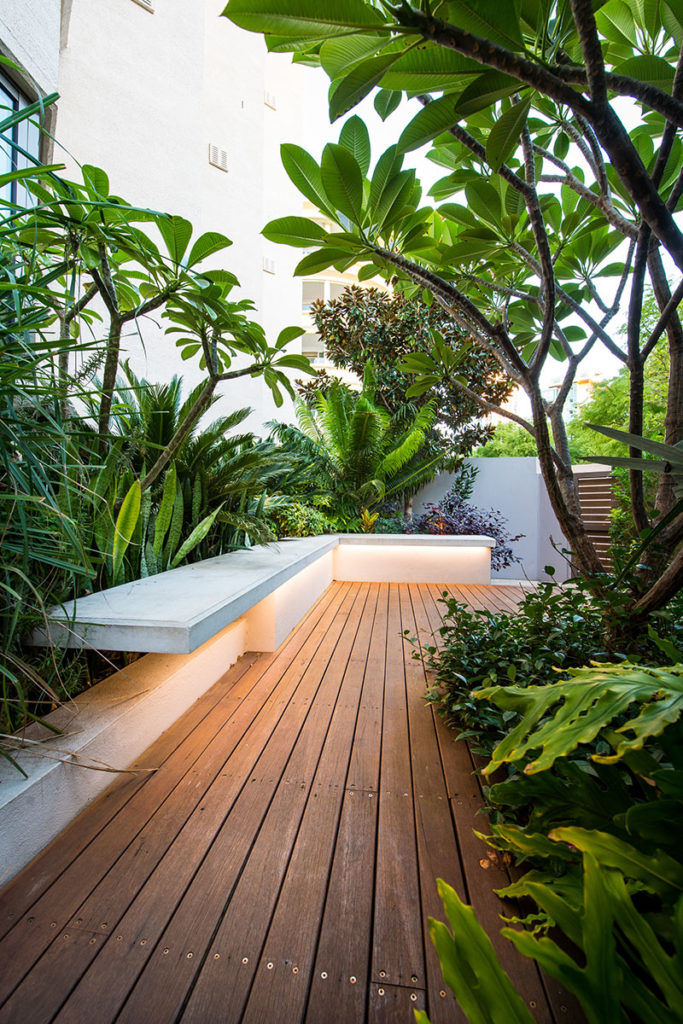 Outdoor cantilevered seat in lush garden
