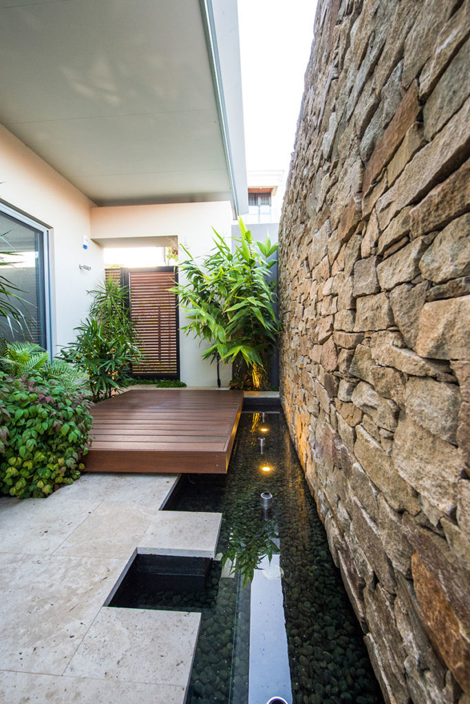 bathroom courtyard with water feature and yoga platform and beautiful stone wall