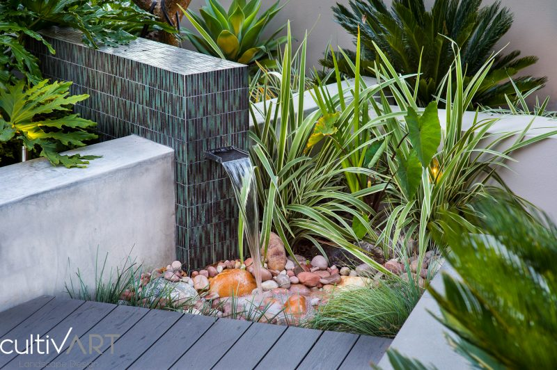 water feature with mosaic tiles and stainless steel water spout designed as part of composite decked area with washed river stones and dado finish wall